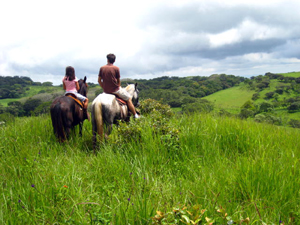 Two horseback riders enjoy the beautiful property and distant views.