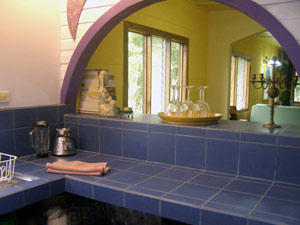 The kitchen in the main house is nicely remodeled with tile and an arched pass-through.