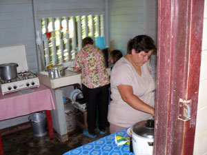 Grandmother, granddaughter, and daughter-in-law work on lunch in the secondary kitchen.