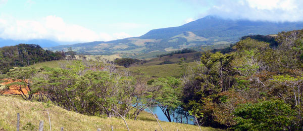 The large pond is here glimpsed through the trees and in the distance appears the cloud-topped Tenorio Volcano.