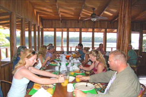 Guests enjoy a family-style meal with a broad and breezy river view.