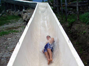 A swimmer zooms down the slide to the pool.