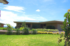 The house sits in landscaped grounds above Lake Arenal.