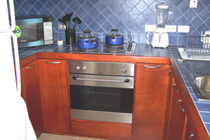 The kitchen has first-class wood, tile, and appliances.