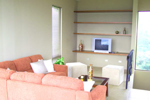 The living room has built-in shelving and view windows.