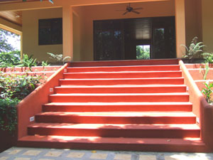 The solidly built home entrance stairway to a house-wide frontal veranda.