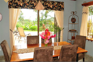The dining room has large windows and access to the broad patio and pool.
