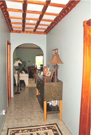 The hallway leads from the front entrance past the bedrooms and laundry room to the living room,