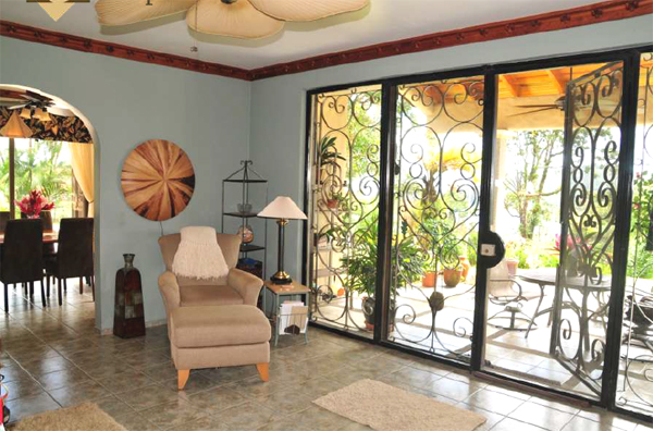The large living room has a full wall of glass doors opening to the broad covered patio.