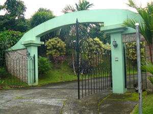 The formidable entrance gate is at the top of a paved road that serves the 6-property decade-old well planned development.