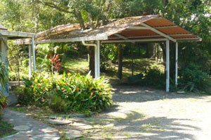 The carport sits between the cottage and the pond and aviary.