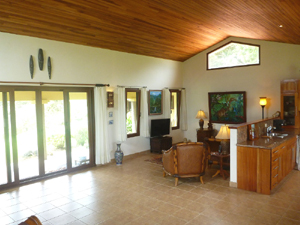 The open plan LR/kitchen building has a cathedral ceiling and a long array of sliding glass doors opening to the veranda and pool.