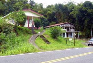 The house sits above the road next to a small commercial building that is also for sale.