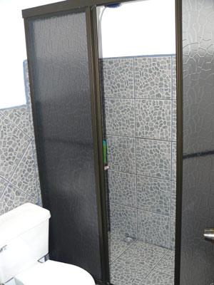 The bathroom has new fixtures, including a large shower stall.
