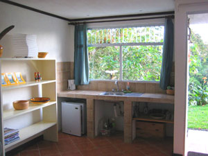 The kitchenette has a wide tile counter and a sink as well as a small refrigerator.