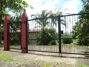 The property has a handsome gate and wrought iron fence.