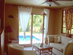 Through sliding doors with wrought iron screens, the pool can be seen outside the comfortably furnished living room.