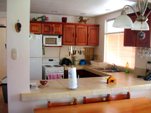 The kitchen is a large pleasant place with plenty of counter space and cupboards.