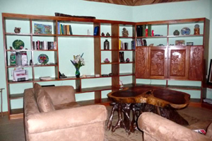 The living room has extensive shelving of fine hardwood.